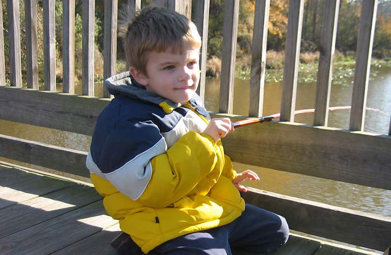 Kid fishing with a cane pole rod